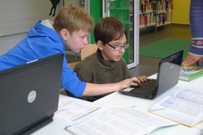 Two students work at the computer in the learning centre